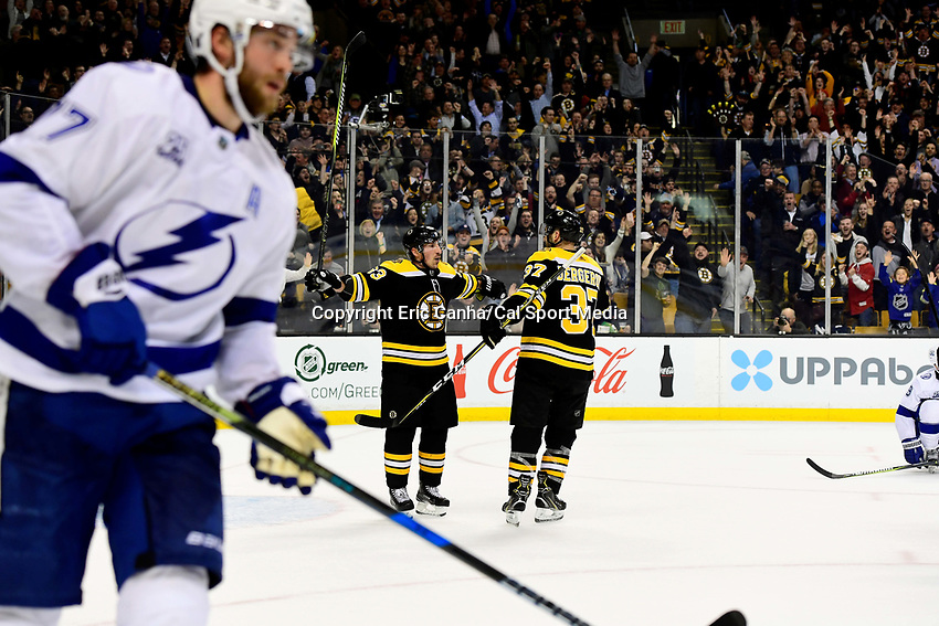 March 29, 2018: Boston Bruins left wing Brad Marchand (63) (left) celebrates a third period goal with center Patrice Bergeron (37) during the NHL game between the Tampa Bay Lightning and the Boston Bruins held at TD Garden, in Boston, Mass. Boston defeats Tampa Bay 4-2. Eric Canha/CSM