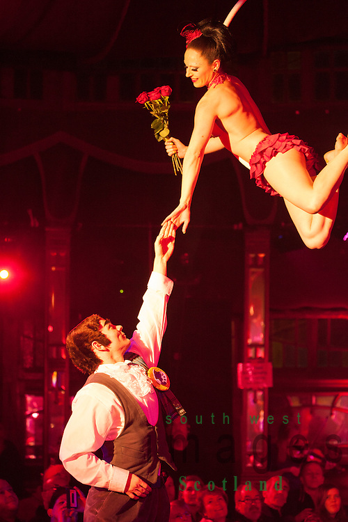 Big Burns Supper 2014, Dumfries, Le Haggis, almost naked female acrobat hanging finely balance from a hoop suspended from the ceiling while a look alike Robert Burns gives her flowers in the Spiegeltent,