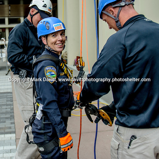 "Easy to smile after reaching the ground, Captain Amy Kramer from the Pleasant Hill Police Department went ""Over the Edge"" of the 345-ft. Financial Center in Des Moines in support of Special Olympics Iowa Oct. 26."