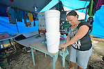 Welma Chuca gets clean water from a water filter in her family's temporary home in Tanauan, a city in the Philippines province of Leyte that was hit hard by Typhoon Haiyan in November 2013. The storm was known locally as Yolanda. Hundreds of families here received water filters from the United Methodist Committee on Relief, a member of the ACT Alliance. UMCOR is also working with city officials to help residents here build permanent houses to replace those they lost in the storm.