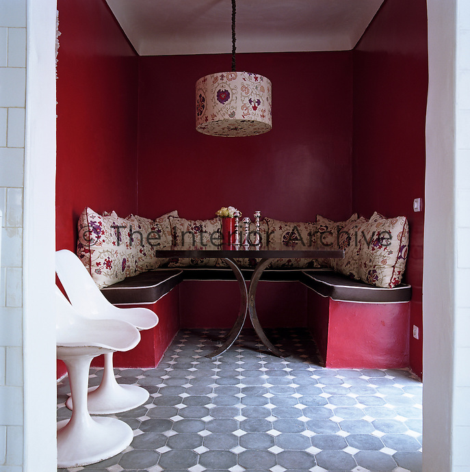 This small red dining room has been decorated in a bold manner with pillar box red walls, patterned cushions and  geometrically laid floor tiles