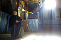 Greek-Orthodox priest Father Neofitis, 82, enjoys the warmth of sunbeams streaming in the Church of the Nativity December 20, 2001 at the top of the stairs leading to the Grotto where according to tradition Jesus was born, in Bethlehem. With less than a week to go before Christmas, the biblical town of Bethlehem in the West Bank is virtually empty of the usual hordes of visitors who have canceled their trips to the Holy Land because of the 15-month-old Israeli-Palestinian conflict. Photo by Quique Kierszenbaum