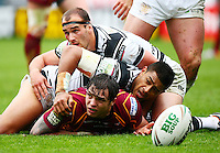 PICTURE BY VAUGHN RIDLEY/SWPIX.COM - Rugby League - Super League - Huddersfield Giants v Hull FC - Galpharm Stadium, Huddersfield, England - 09/04/12 - Huddersfield's Scott Grix is tackled by Hull FC's Willie Manu and Danny Houghton.