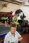 © Joel Goodman - 07973 332324 . 28 August 2013 . Wood Street Mission , Manchester , UK . Volunteer Wendy Witts (70 from Kearsley) (correct) carries clothes from a large pile of unsorted donated goods (behind). Photo credit : Joel Goodman