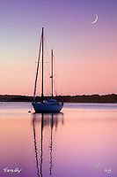 a sailboat at dusk with reflections
