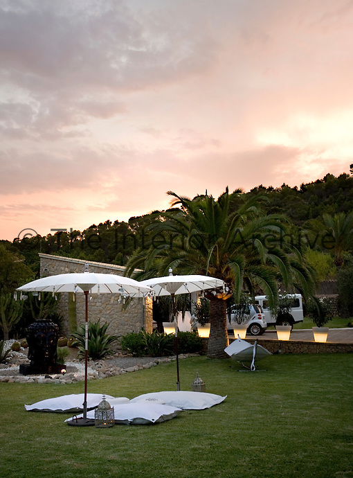 The warmth of an evening sky is reflected in the outdoor lighting on the approach to the villa