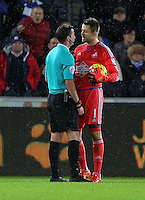 Lukasz Fabianski of Swansea (R) speaks to match referee Michael Oliver after Robert Huth of Leicester City pushed him over during the Barclays Premier League match between Swansea City and Leicester City at the Liberty Stadium, Swansea on December 05 2015