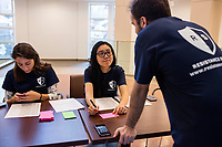 Claris Chang (center), 25, Joseph Manganiello (right), 24, and Meredith Davis, 26, all Master in Public Policy grad students at Harvard, wait to register attendees before a session of Resistance School at Harvard University's John F. Kennedy School of Government, on Thurs., April 27, 2017.