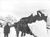 This appears to be a double-headed freight train led by an engine with large wedge pilot snowplow.  Three men posing.  This is probably on the Silverton Branch.  There appears to be a railroad building of some sort at left center.<br /> D&amp;RGW  Silverton Branch, CO
