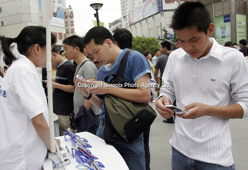 Pedestrians look at Philips mobile phones at a street-side display in Shanghai, China..