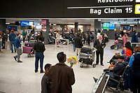 A man waits with a bouquet of flowers as passengers arrive at the international terminal at Dulles International Airport in Dulles, Va., Monday, March16, 2020. Some people are taking the precaution of wearing face masks as they arrive to be greeted by family and or friends. Credit: Rod Lamkey / CNP/AdMedia