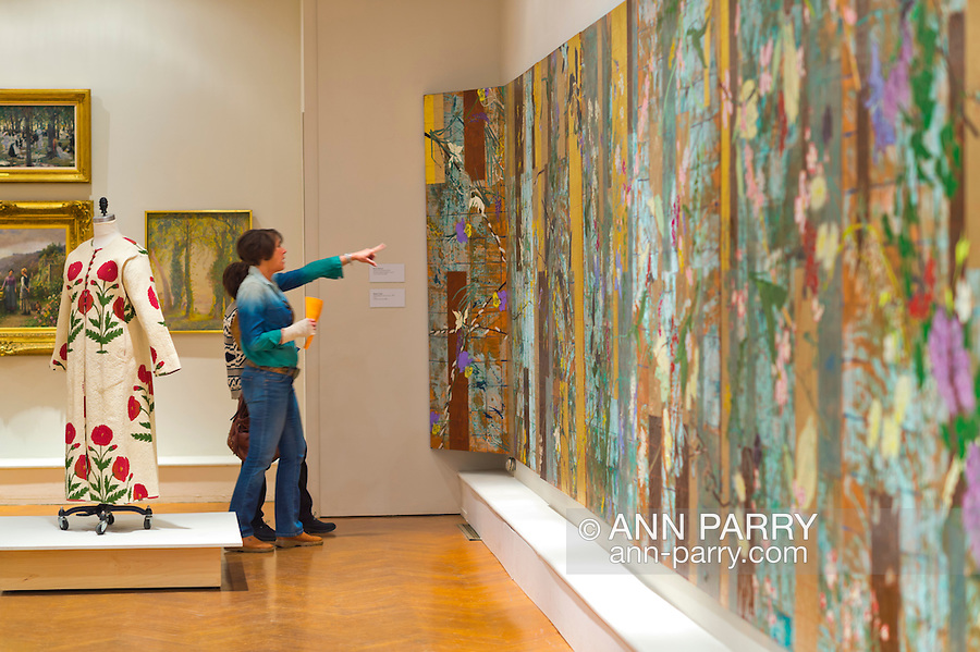 Roslyn, New York, U.S. - April 12, 2014 - During International Slow Art Day, visitors view the long wall canvas Spring Scatter Summation by Robert Kushner and cotton Block Printed Coat by Brigitte Singh at the Garden Party exhibit at the Nassau County Museum of Art on Long Island. During this annual worldwide event, those participating went to local museums and viewed a small number of works of art, each for at least 10 minutes, and then discussed them afterward.