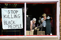 """Store owner Greta Allendorf (right) and the store's original owner and founder Harriet Wells work together Friday, June 19, 2020, while dressing mannequins for a Black Lives Matter-themed window display at Cheap Thrills, a vintage clothing and costume store, on East Avenue in downtown Fayetteville. """"We can't just put clothing up here right now,"""" Allendorf said. Visit nwaonline.com/200620Daily/ for today's photo gallery.<br /> (NWA Democrat-Gazette/Andy Shupe)"""