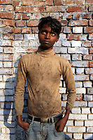 A child worker stands in one of the many small and informal leather-producing tanneries in Kanpur.