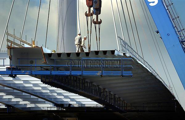 UTRECHT - In Utrecht is langs het Amsterdam-Rijnkanaal zondag het eerst stalen brugdek ingehezen van de Papendorpse brug. Deze bijzondere, door de Erasmusbrug-architect Ben van Berkel ontworpen, tuibrug, gaat de historische Domstad verbinden met de vinexlokatie Leidsche Rijn. De 750 meter lange brug wordt gebouwd door Nederlands/Belgische bouwcombinatie CFE/Victor Buyck, wordt in segmenten in elkaar gezet, heeft een bijna honderd meter hoge pyloon en kost ruim 25 miljoen euro kosten. NO INTERNET