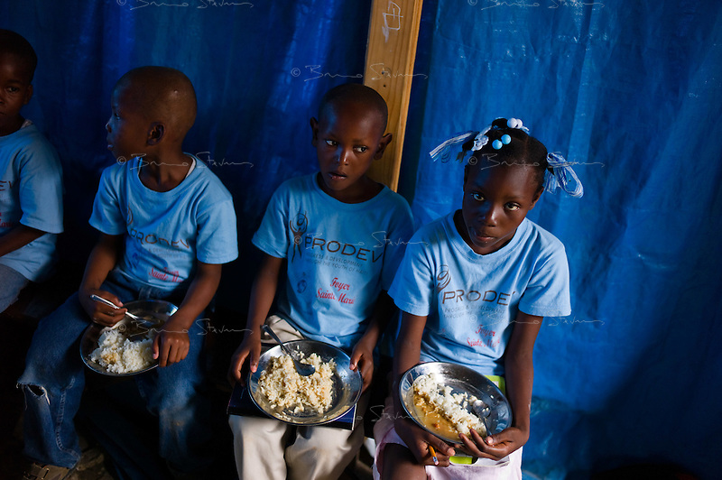Port au Prince, Haiti, April 12, 2010.A WFP sponsored school feeding for almost 500 pupils from the  'Communauté Sainte Marie' school in the almost totally destroyed 'Canapé Vert' area. The 3 months anniversary of the earthquake, as the rainy season arrives making life conditions for 2 millions homeless Haitians miserable.