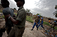 Indian female Peacekeepers from the Indian FPU ( formed police unit ) escort a liberian police officer while arresting a suspect during a cordon and search operation in the  in Monrovia, Liberia on Monday March 19 2007. .103 Indian police personnel  were specially selected to take part in the UNMIL peacekeeping mission in Liberia for an initial deployment of 6 months. .They are the first contingent entirely formed by women in the history of the United Nations Peacekeeping..their mission in the country is to provide fire support to the unarmed liberian security forces. In india these women distinguished themselves by operating in the most troubled areas of the country taking part in counter insurgency and crowd control special operations.