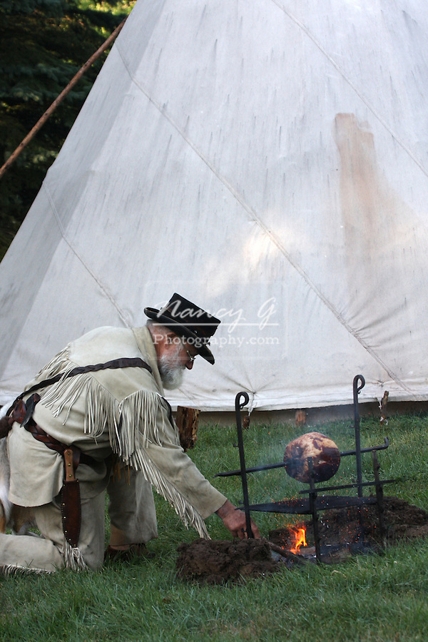 A buckskinner in front of a tipi making a ham for dinner