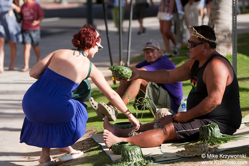 Woman buying lahala grass products from local street vendor in Waikiki, Honolulu, Oahu, Hawaii