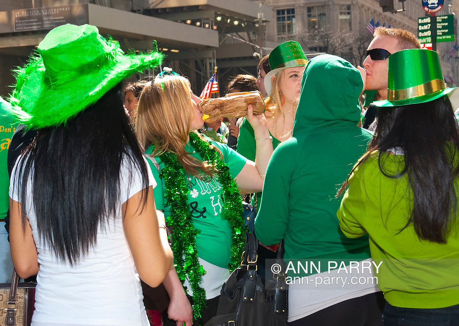 MARCH 17, 2011 - MANHATTAN: Young people dressed in green elebrating at St. Patrick's Day Parade across from St. Patrick's Cathedral in background, on 5th Avenue and E 51 Street, NYC, New York, USA.