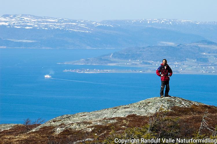 Mann på Gråkallen i Trondheim en vårdag. Hurtigruta på Trondheimsfjorden i bakgrunnen  ----- Man on hill with Trondheimsfjorden in the background