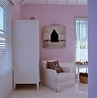 A simple white wardrobe and armchair in the corner of the pink master bedroom