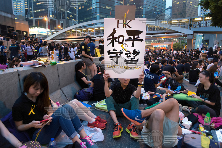 A protesters with the 'Occupy Central ' movement which is organising events of civil disobedience to protest against the Chinese government's electoral policy for Hong Kong holds up a sign which reads 'Keep Watching for Peace - Umbrella Revolution'. Hong Kong was supposed to be having direct elections for the post of chief executive by 2017 but the government in Beijing has said that the election will only be from a list of pre-approved candidates.