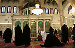 Damascus, Syria. Muslim women pray at the shrine of the prophet John the Baptist, The Umayyad Mosque. Umayyad Mosque located in the old city of Damascus, is one of the largest and oldest mosques in the world and is considered the fourth-holiest place in Islam. The mosque holds a shrine which today may still contain the head of John the Baptist, honored as a prophet by both Christians and Muslims.