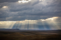 Sun rays fall on the Rocky Mountain Front outside Simms, Montana, USA, before a thunderstorm.