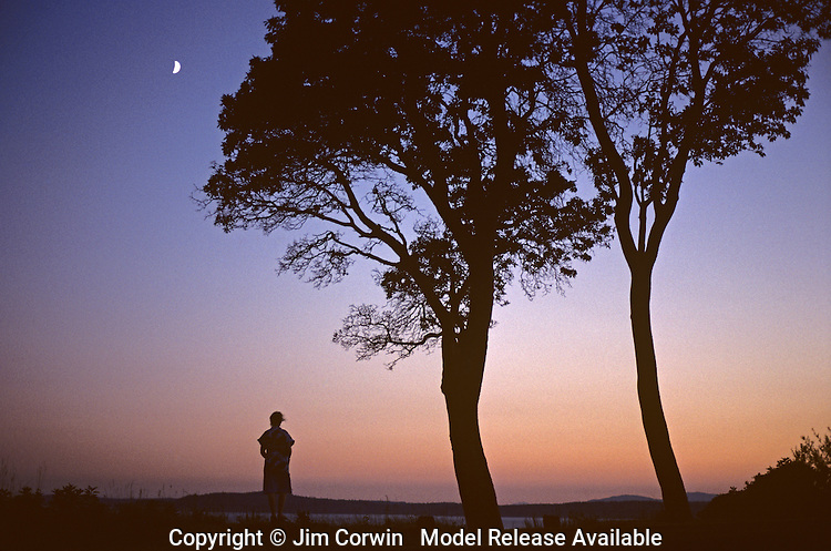 Woman standing on bluff looking out over Puget sound with crescent moon Magnolia Bluff Seattle Washington State USA  MR