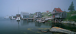 Lunenburg County, Nova Scotia<br /> Boat houses and fishing boats on the rocky hillside at Blue Rocks village on foggy Lunenburg Bay
