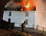 A lone firefighter brings a hose into position as fire burns through the roof of a home,  as firefighters work an exterior attack operation, Tuesday, February 23, 2016, in Manchester. The fire broke out around 7:30 at a home on North Elm Street. The Eighth Utilities Fire Department responded requesting assistance from Manchester Fire Rescue and EMS. Fire extended through out the house and through the roof forcing firefighters to exit the dwelling and work from exterior only. Multiple towns came to the scene or helped cover the open stations in Manchester during the two-alarm fire. All the occupants got out of the home safely and no firefighters were injured. (Jim Michaud / Journal Inquirer)