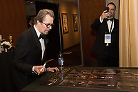 Gary Oldman signs a poster backstage with the Oscar&reg; for performance by an actor in a leading role, for work on &ldquo;Darkest Hour&rdquo; during the live ABC Telecast of The 90th Oscars&reg; at the Dolby&reg; Theatre in Hollywood, CA on Sunday, March 4, 2018.<br /> *Editorial Use Only*<br /> CAP/PLF/AMPAS<br /> Supplied by Capital Pictures