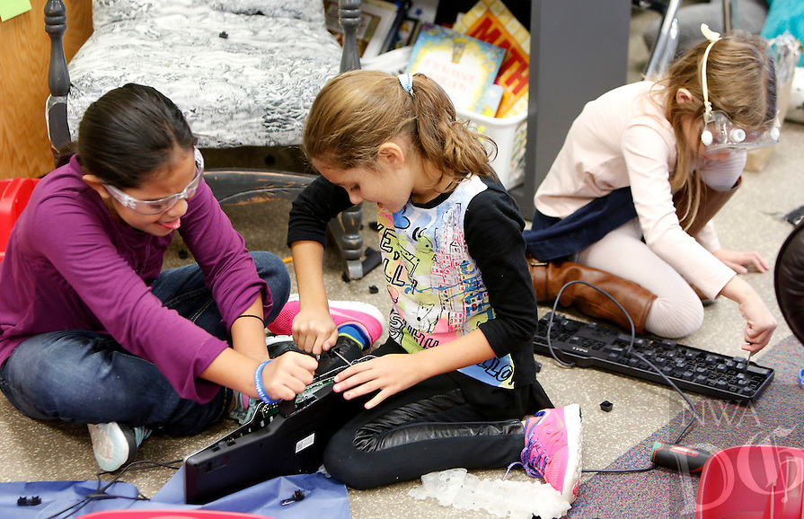 NWA Media/DAVID GOTTSCHALK - 11/7/14 - Karen Sanchez, left to right, Alivia Peris (cq) and Rory Connor, third grade students in the class of Landi (cq) Tarp at Willowbrook Elementary School in Bentonville, take apart keyboards Friday November 7, 2014 as they participate in Maker Day. Students dismantled discarded electronics and will recycle the parts into ornaments and decorations.  The upcycled items will be sold at Downtown Bentonville Inc.'s Tree Lighting Festival on Saturday, November 22 on the Bentonville Square. All proceeds will be donated to The Water Project, a non-profit organization that develops sustainable water projects for communities without sufficient access to clean water and proper sanitation.