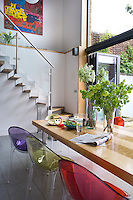 In the dining room a system of sliding glass doors opens an entire wall to the garden beyond and an elegant staircase connects the living and dining areas
