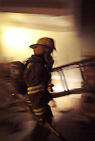 Volunteer firefighters practice fighting a school fire during a training exercise