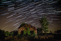 Old rock building nerr Altus Arkansas with star trails.