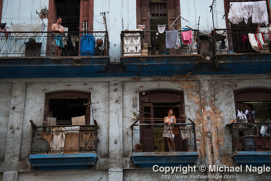HAVANA, CUBA -- MARCH 25, 2015:   People look out from their terraces in Havana, Cuba on March 25, 2015. Photograph by Michael Nagle
