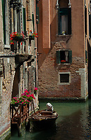 Narrow canal and old brick buildings showing balconies and traditional brickwork. Venice Italy.