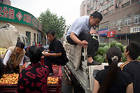 Market sellers talk with shoppers from their trucks in Qingdao, Shandong, China.