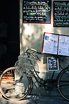 Bicycle parked below a chalkboard menu, outside of an Avignon cafe, France