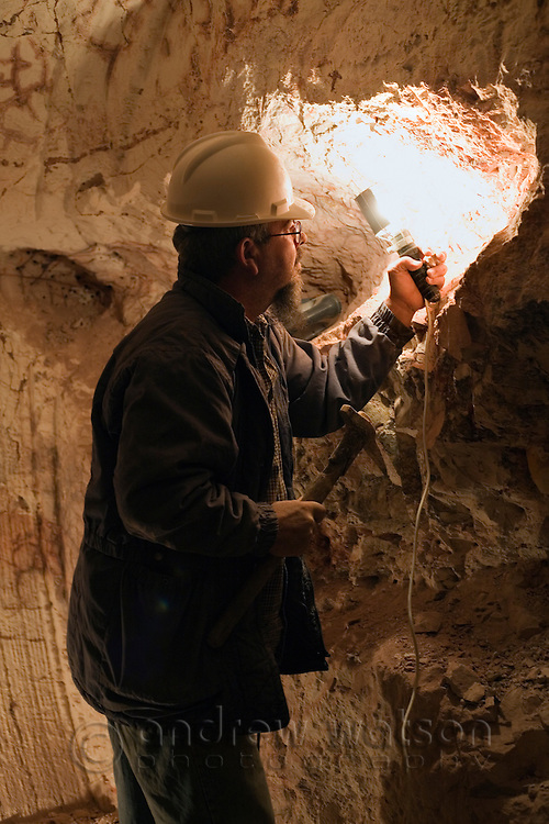 Opal miner working underground with a pick.  Coober Pedy, South Australia.