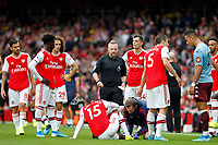 Ainsley Maitland-Niles of Arsenal receives treatment whist referee, Jonathan Moss waits to send him off during the Premier League match between Arsenal and Aston Villa at the Emirates Stadium, London, England on 22 September 2019. Photo by Carlton Myrie / PRiME Media Images.