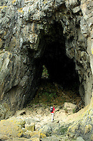 A walker underneath the Black Cave near Kildonan on the Arran Coastal Path; Isle of Arran, Ayrshire<br /> <br /> Copyright www.scottishhorizons.co.uk/Keith Fergus 2011 All Rights Reserved