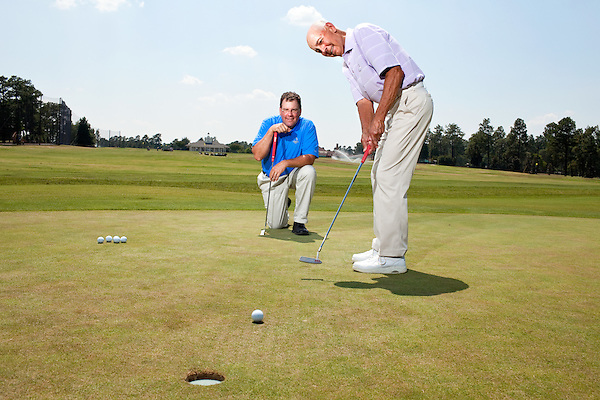 June 24, 2010. Pinehurst, North Carolina..Eric Alpenfels, a golf coach at Pinehurst, and Dr. Bob Christina, a former dean at UNC-Greensboro, have developed a theory that putting is more successful when the player looks at the hole rather than the ball while hitting their shot.. Eric Alpenfels, left, watches Bob Christina putt on the practice green of the Pinehurst Golf Resort..