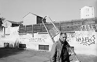 Milano, quartiere Dergano, periferia nord. Un vecchio muro semi abbattuto e un uomo con una scala --- Milan, Dergano district, north periphery. An old wall semi demolished and a man with a ladder