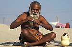 A Sadhu combing his beard. It was estimated that 30 million people visited the Maha Kumbha Mela in 1989 making it the largest gathering of any kind in modern history.Sadhus holy men and pilgrims come to bathe at the Sangam where the Ganges,Yamuna and Saraswati Rivers meet. Maha Kumbha Mela is held every twelve years at Prayag (Allahabad) in Uttar Pradesh in India.