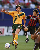 The MetroStars' Joselito Vaca looks to tackle the ball away from the Galaxy's Andreas Herzog. The NY/NJ MetroStars defeated the LA Galaxy 3 to 0 during MLS action at Giant's Stadium, East Rutherford, NJ, on August 8, 2004.