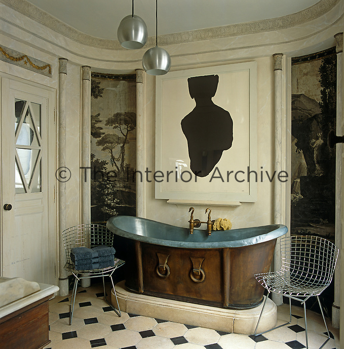 An antique zinc bath with wooden sides has a set of swan-head brass taps and is flanked by a pair of Bertoia wire chairs