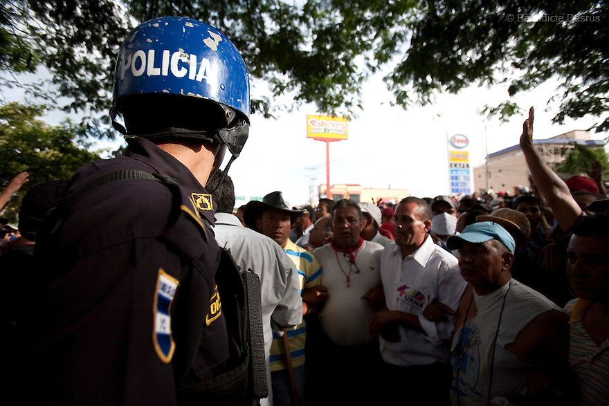 5 July 2009 - Tegucigalpa, Honduras  Protesters plead with polices to join them after soldiers shot and killed one of them. Supporters of ousted Honduras' President Manuel Zelaya holds bullets shot by soldiers at the protesters at the international airport in Tegucigalpa. At least one person was killed and ten were badly wounded when protesters demanding the return of ousted Honduran President Manuel Zelaya clashed with troops at the Tegucigalpa airport. Zelaya turned back from an attempted return home on Sunday after soldiers clashed with his supporters as he tried to land, fueling tensions over the coup that toppled him. Photo credit: Benedicte Desrus